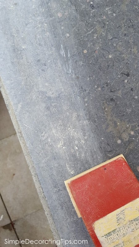 SimpleDecoratingTips.com with sanding block sanding off yucky stuff from marble